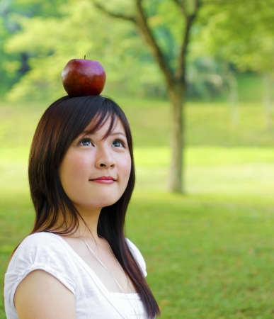 Beautiful young Asian woman with red apple on her head. photo