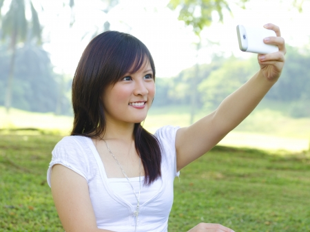 Asian girl self photographing, outdoor green park photo