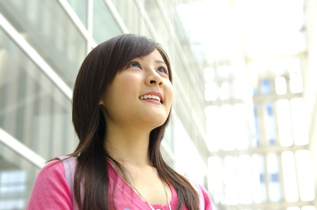 pan asian: A young Asian girl looking far away to bright light in front of a modern building. Stock Photo