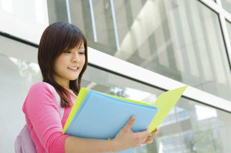 university building: Asian teen student reading file folder outside school building Stock Photo