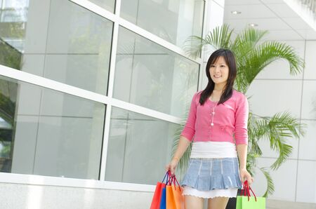 Asian young shopper walking out from shopping mall photo