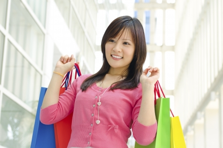 Happy young Asian shopper holding shopping bag in shopping mall photo
