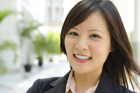 asian woman face: Asian female with her cheerful smile, outside modern building.
