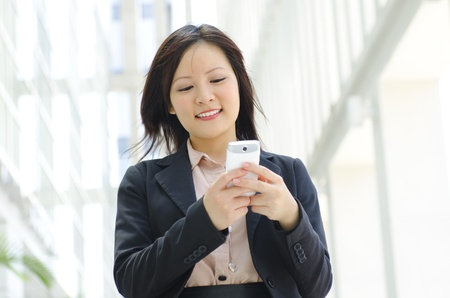 Happy oriental Asian young executive using mobile phone to online  texting  sms photo