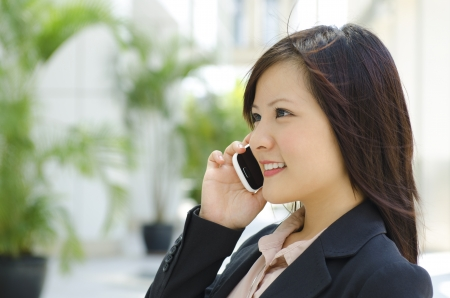 Young Asian business woman talking phone outside modern building photo
