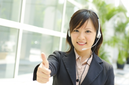 Friendly Customer Representative with headset thumb up during a telephone conversation. photo