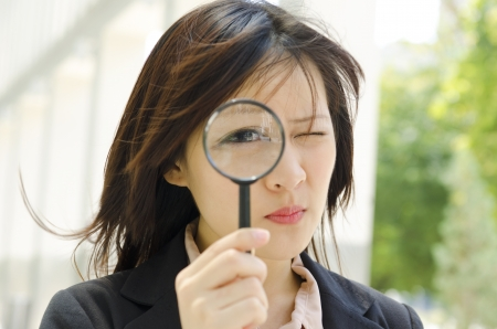 Asian business woman with magnifying glass to the eye photo