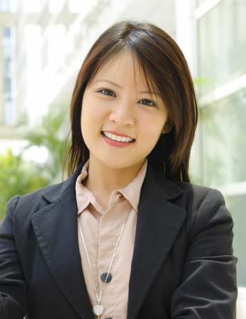 asian office lady: Young Asian executive standing outside office building