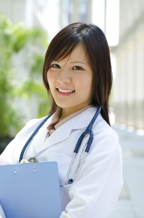 A young Asian Chinese medical student standing in front modern building photo