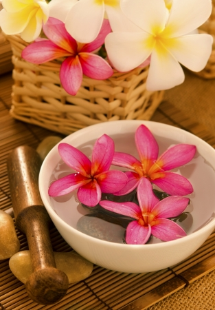 Tropical spa with Frangipani flowers on water. Low lighting, suitable for spa related theme. photo