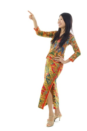 Full body Asian female with batik dress pointing on empty space, over white background photo