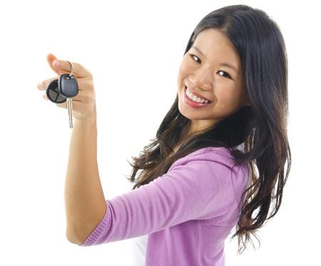 Femme heureuse jeune Pan asiatique montrant sa clé de voiture nouvelle, isolé sur fond blanc, se concentrer sur la clef de voiture