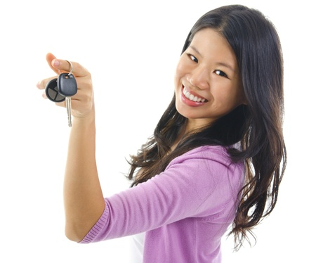 Happy Young pan asian woman showing her new car key, isolated on white, focus on car key photo