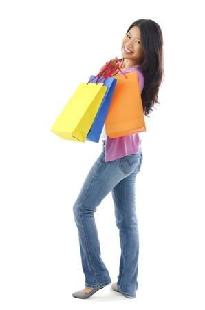 Full body cheerful Asian shopper over white background photo