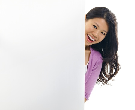 Cheerful young Asian woman hiding on a blank space. Stock Photo - 15200361