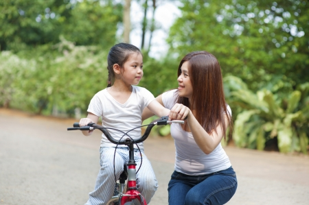 Asian mother teaching little girl to ride a bike photo