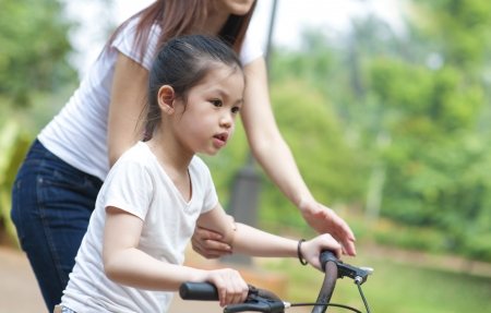 Asian Mother teaching daughter cycling at the park in the evening photo