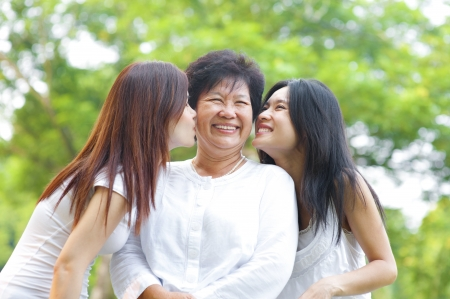 mum and daughter: Young Asian daughter kissing their senior mother, outdoor park