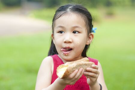 Little Asian girl eats a sandwich and licking lips on fresh air photo