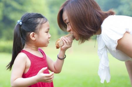 Little Asian girl feeding her mother sandwich outdoor photo
