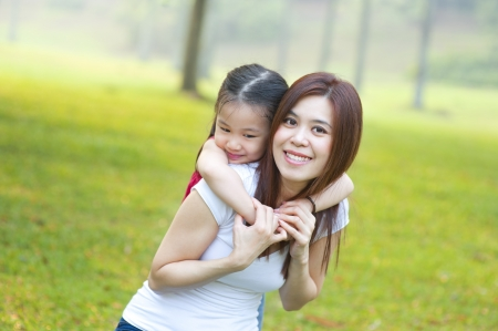 Asian mother and daughter having fun in park photo