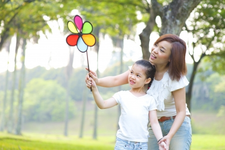Asian family playing windmill at outdoor park photo