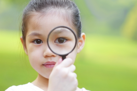 eyesight: A little girl peers at the camera through a magnifying glass.