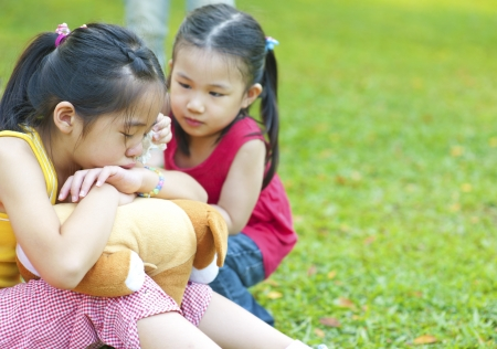 Little girl is comforting her crying sister photo
