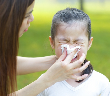 sneeze: Cute little Asian girl with the flu, outdoor park
