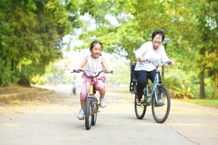 Little Asian girl and grandmother riding on bicycle with great fun photo