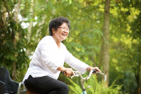 asian sport: 60s senior Asian woman riding on bicycle outdoor with great fun