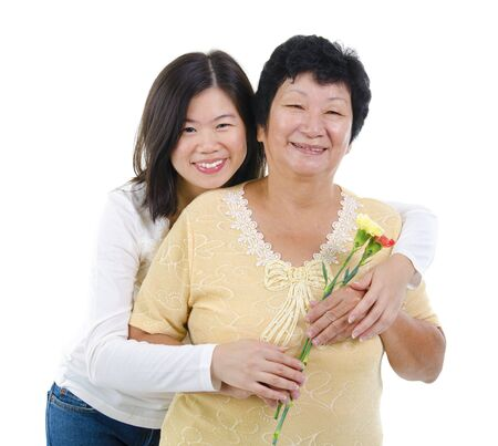 Daughter giving carnation flowers to her mother over white background photo