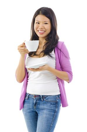 tomando refresco: Una mujer china asi�tica oriental con una maravillosa sonrisa t� con dientes o beber caf� en una taza blanca y platillo