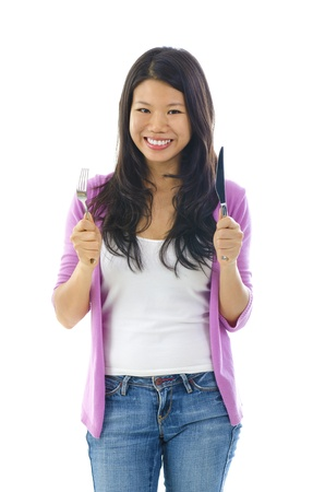 avid: Mixed race Asian woman holding fork and knife ready for food, isolated on white background Stock Photo