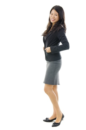 Full body of Asian female in office attire standing over white background photo
