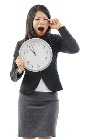 Tired Asian business woman holding a clock and rubbing eye, isolated on white background. photo
