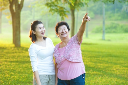 Happy Asian senior mother with her daughter at outdoor park photo