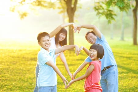 Happy playful Asian family forming love shape, outdoor green park photo