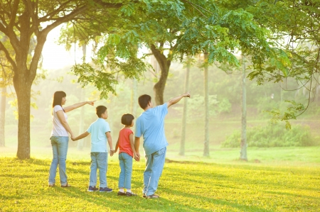 asian family outdoor: Candid Asian family pointing at outdoor park