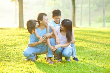 Happy Asian family having conversation at outdoor park photo