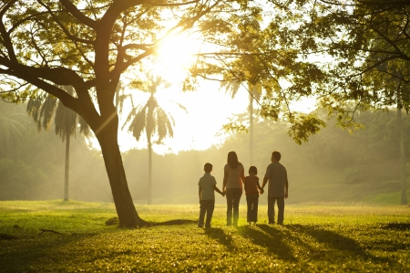 four hands: Asian family holding hands and walking towards light Stock Photo