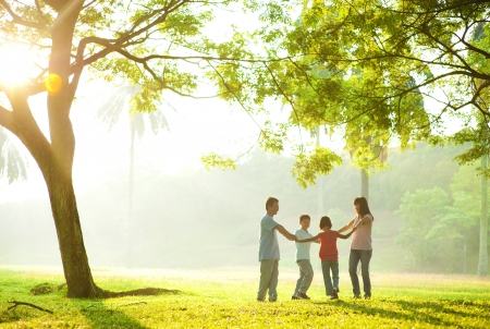Happy Asian family holding hands in a circle and running over green lawn photo