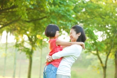niños platicando: Asia madre abrazando a su hija en el parque al aire libre Foto de archivo