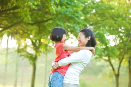 Asian mother hugging her daughter at outdoor park photo