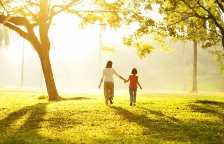 Vista posterior de la madre asiática sosteniendo la mano de su hija a correr hacia la luz Foto de archivo