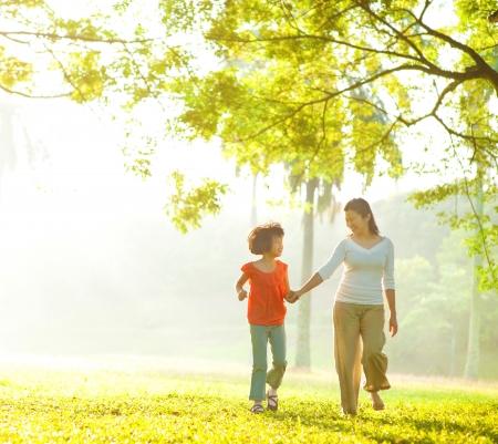 madre con hija: Asia madre e hija de la mano caminando en el parque al aire libre Foto de archivo