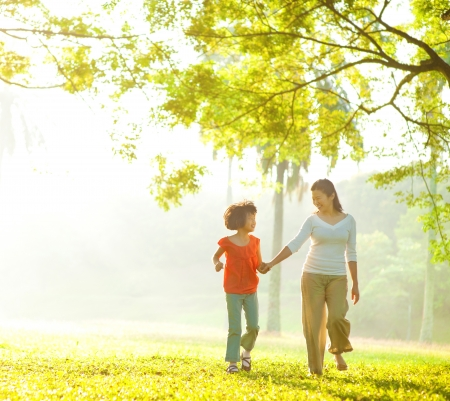 Asian mother and daughter holding hands walking at outdoor park photo