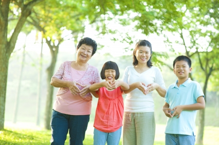 Happy playful Asian family forming love shape at outdoor green park photo
