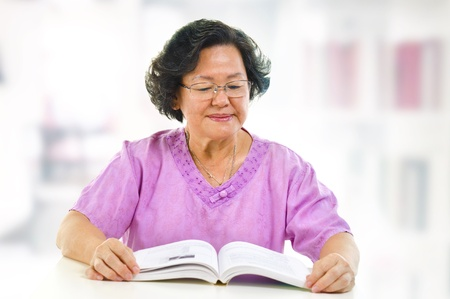 Asian senior woman serious reading book at home photo