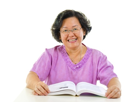 Asian senior woman reading book over white background photo